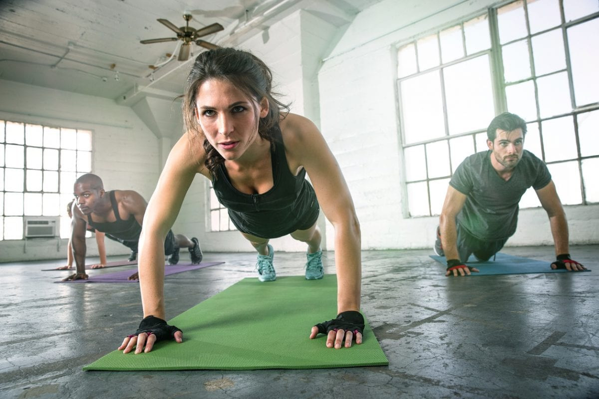 Woman leading a group through a HIIT workout