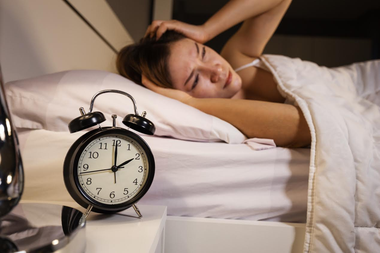 woman waking up with clock showing 2am
