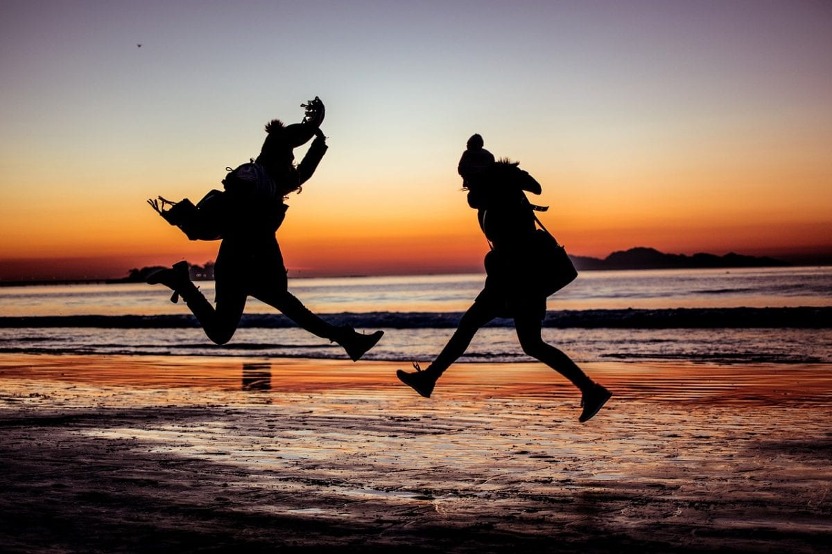 two people jumping in the air at the beach