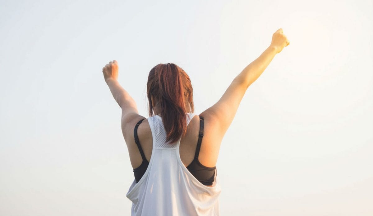 woman standing with arms raised in victory