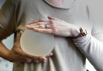 woman holding a breast implant