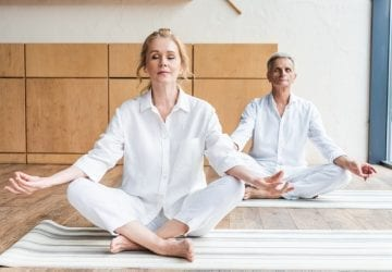 a couple doing yoga in their living room