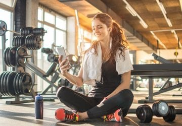 a woman looking at her phone at the gym