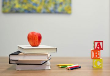 an apple sitting on a pile of books