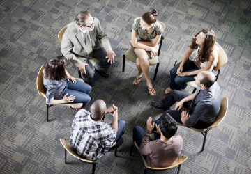 a group attending a meeting in a circle
