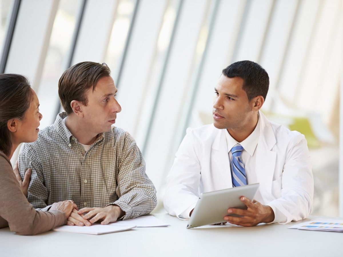 Doctor Using Tablet Computer Discussing Treatment With Patients In Meeting