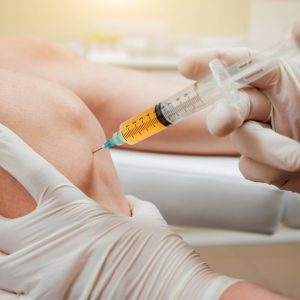 a person getting an injection in their knee